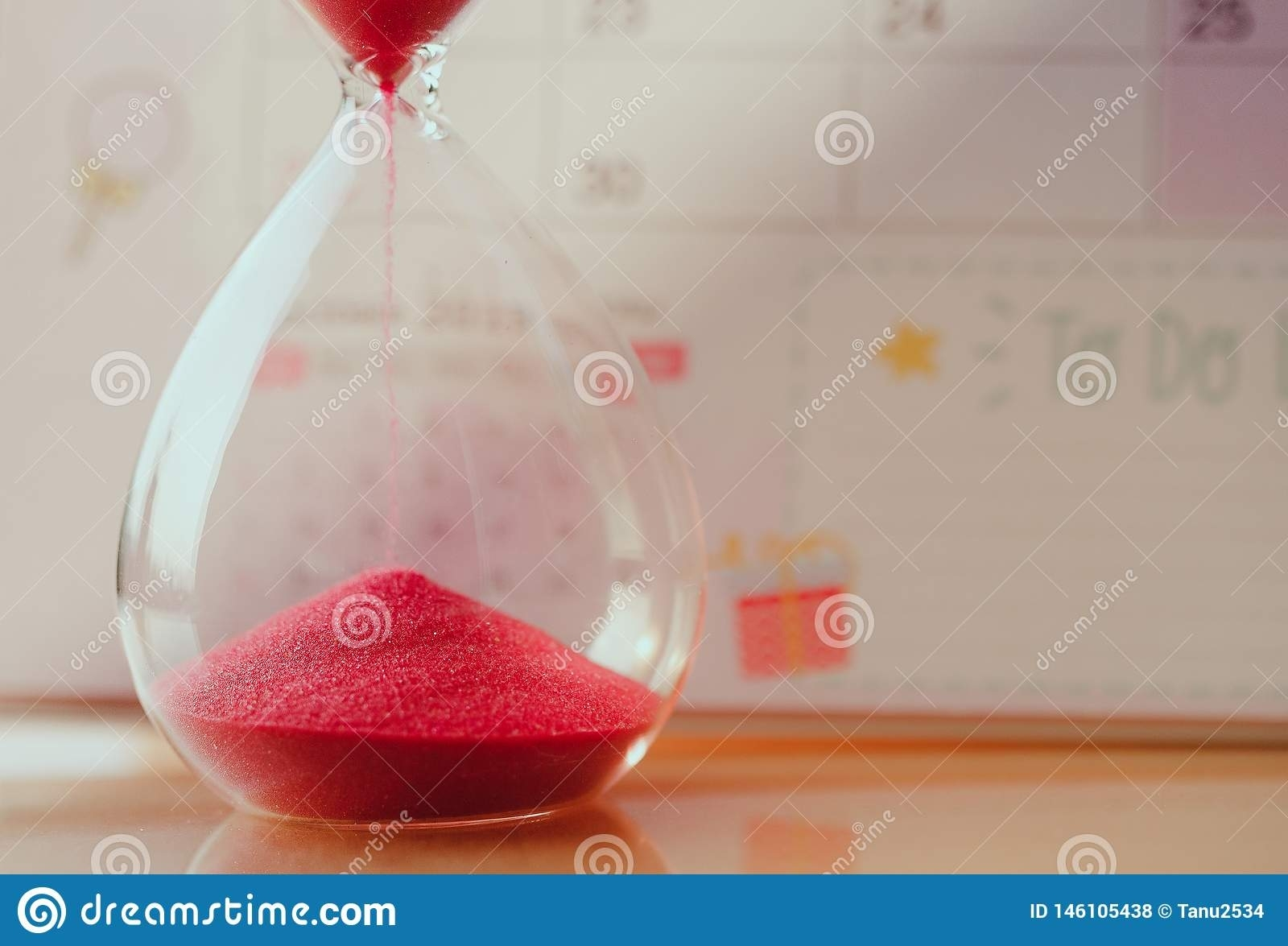 Crystal Hourglass With Red Sand On Calendar Concept For Time