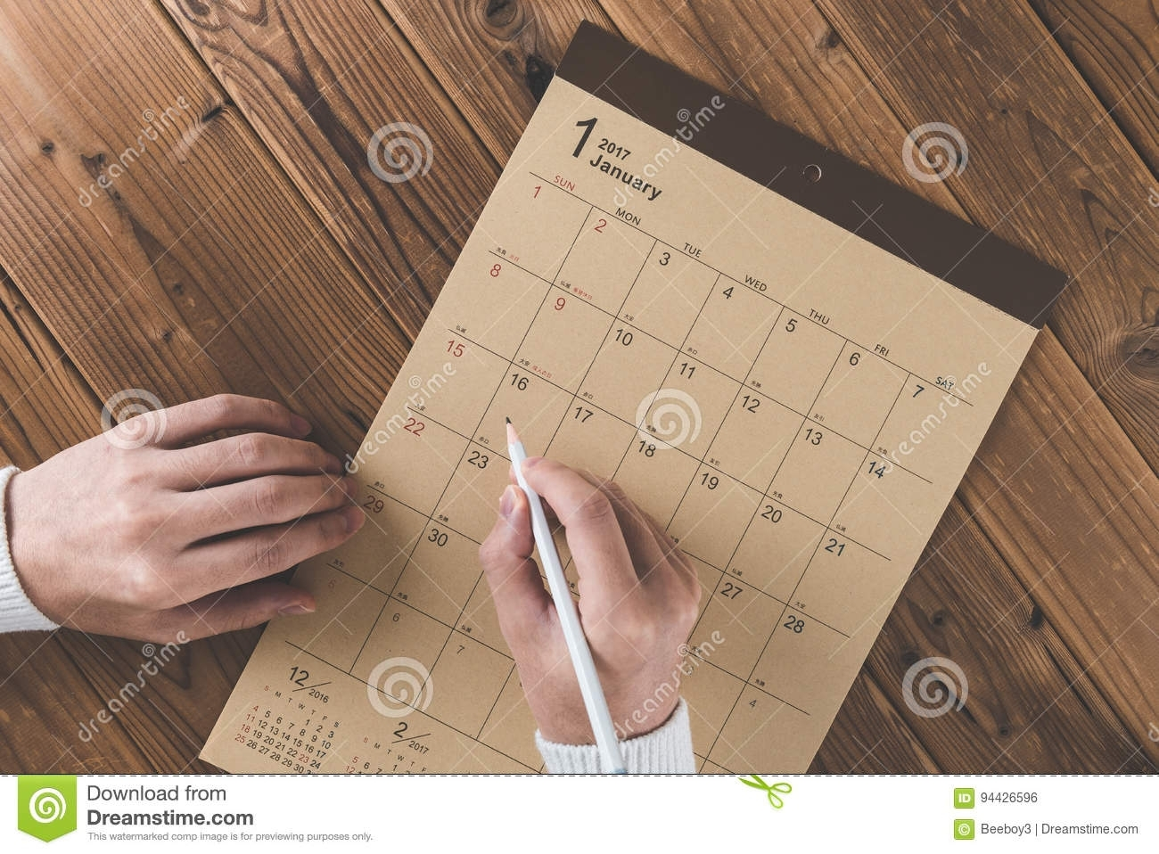 Write A Schedule To A Calendar Placed On A Wooden Table